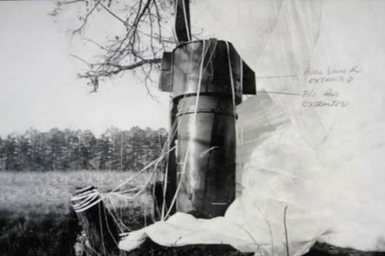 A nuclear bomb and its parachute rest in a field near Goldsboro, N.C. after falling from a B-52 bomber in 1961.
