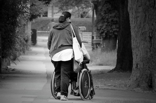 photo of a young woman pushing someone in a wheelchair
