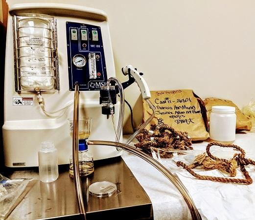 photo of dirty/bloody rope coiled on a table, along with scientific instruments and paper bag labeled with the case number and victims' names.