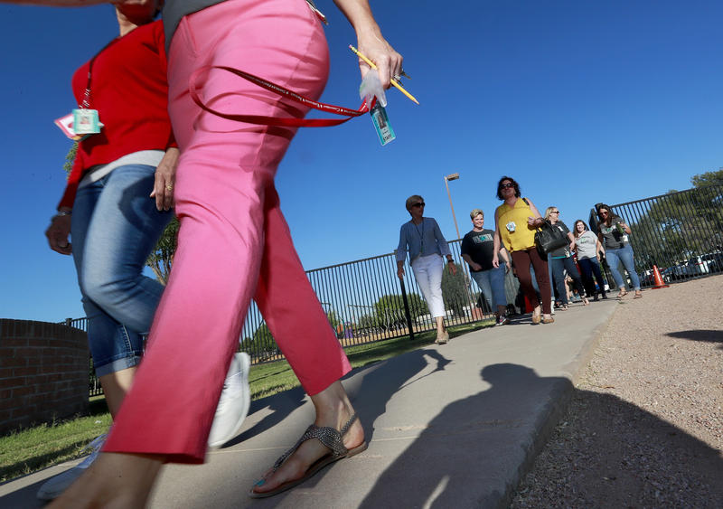 Teachers walk in together as they arrive for work at San Marcos Elementary School Friday, May 4, 2018, in Chandler, Ariz., after a statewide teachers strike ended. (AP Photo/Matt York)