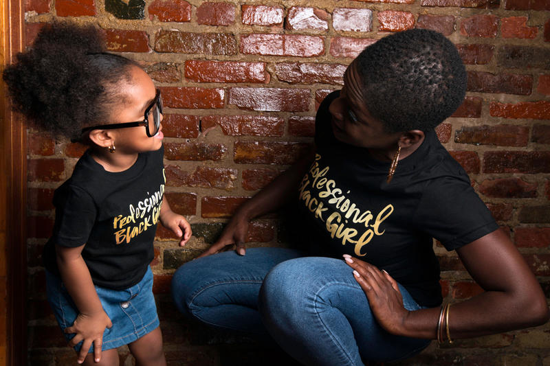 Dr. Yaba Blay and her granddaughter wearing T-shirts which feature the Professional Black Girl logo
