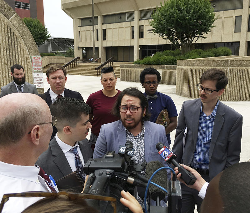 "Plaintiff Joaquin Carcano, center, addresses reporters after a hearing Monday, June 25, 2018, in Winston-Salem, N.C., on their lawsuit challenging the law that replaced North Carolina's ""bathroom bill."" Carcano and other transgender plaintiffs argue the n"