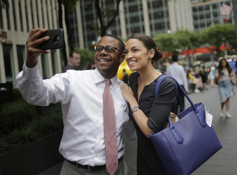 Alexandria Ocasio-Cortez takes a selfie with a pedestrian that congratulated her near Rockefeller Center in New York, Wednesday, June 27, 2018.