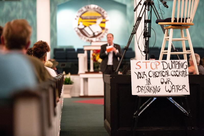 File photo of a protest sign in front of Chemours' President of Fluoroproducts Paul Kirsch during a community meeting hosted by the chemical company Chemours at Faith Tabernacle Christian Center in St. Pauls, N.C. on Tuesday, June 12, 2018.
