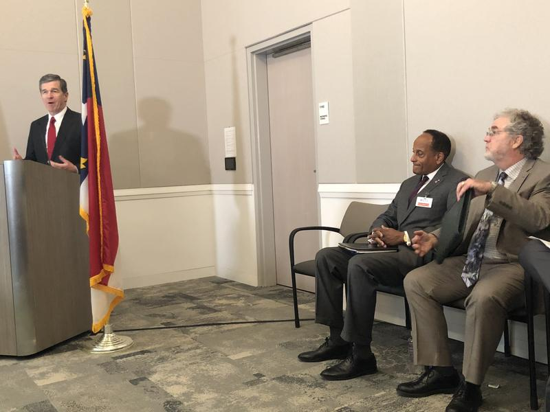Gov. Roy Cooper announces a reduction in the number of homeless veterans. Seated are Secretary of the N.C. Department of Military and Veterans Affairs, Larry D. Hall (left) and Terry Allebaugh of the N.C. Coalition to End Homelessness