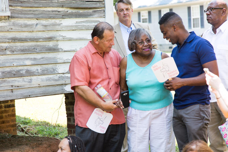 Nina Simone's sister Frances Wayman Fox​ (center) stands outside her childhood home in Tryon, NC during a celebration of its designation as a 'National Treasure. Tryon citizen Crys Armrest (L) and artist Adam Pendleton (R).