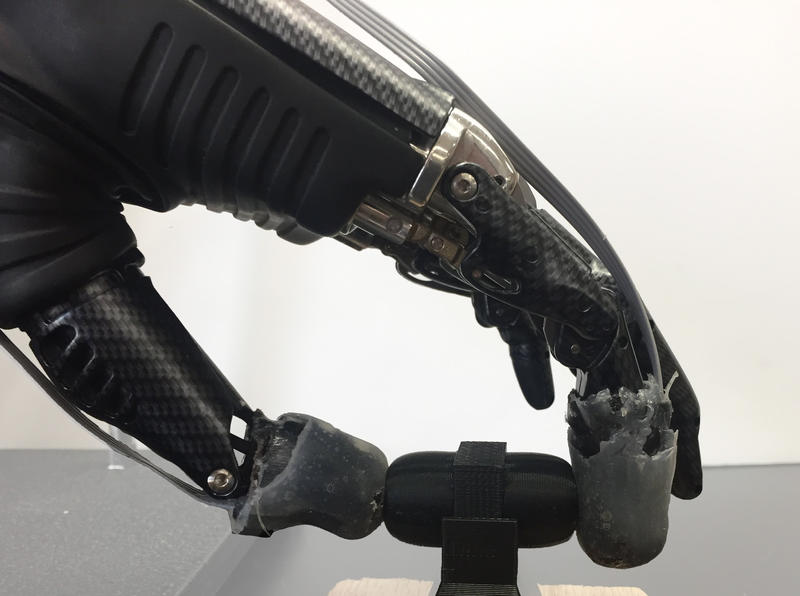 A prosthetic hand grips an object with synthetic skin on its fingertips.
