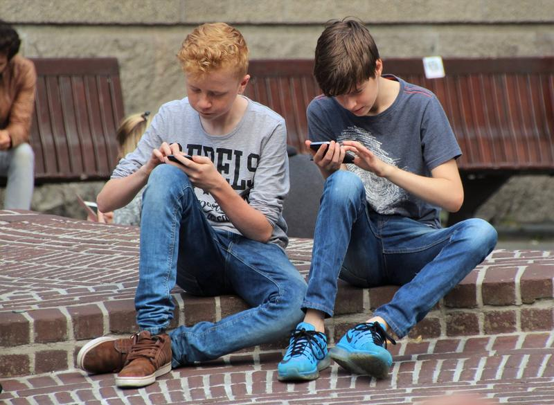A picture of two children playing Pokemon GO on smartphones.