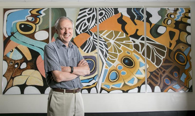 Fred Nijhout poses with crossed arms in front of abstract