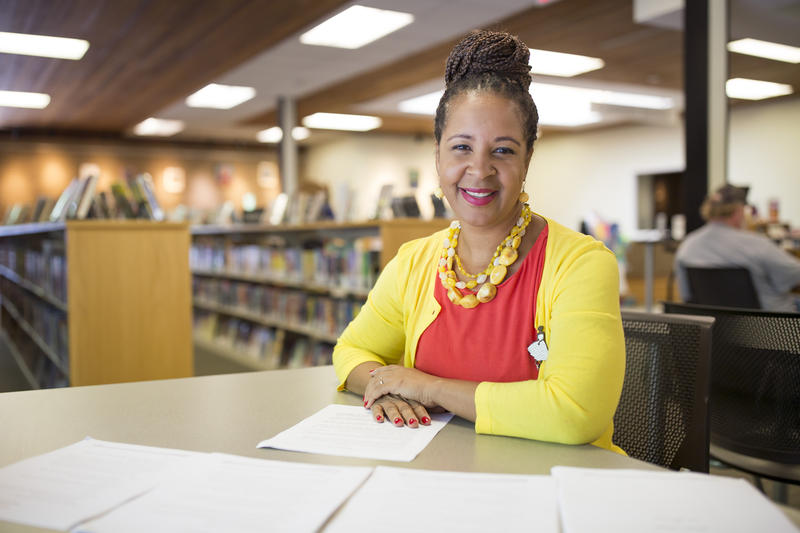 Librarian Judy Allen Dodson sits in the Richard B. Harrison Community Library with pages from her children's books on July 9, 2018.
