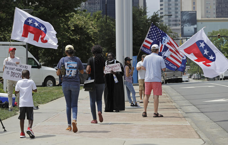 People walk past a group of Trump and RNC supporters outside city hall during a public forum before the Charlotte City Council votes whether to host the 2020 Republican National Convention at a meeting in Charlotte, N.C., Monday, July 16, 2018. (