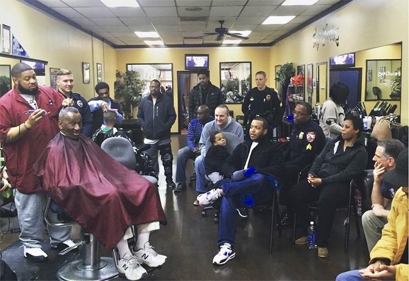 Many people gathered at Headliners Barbershop, while one person cuts hair.