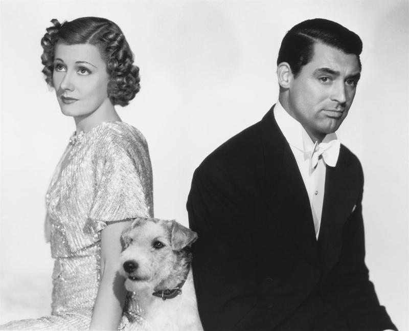 Promotional photo from 1937 screwball comedy 'The Awful Truth' starring actors Irene Dunne and Cary Grant. The actors face away from each other and the scruffy actor dog sits between them.