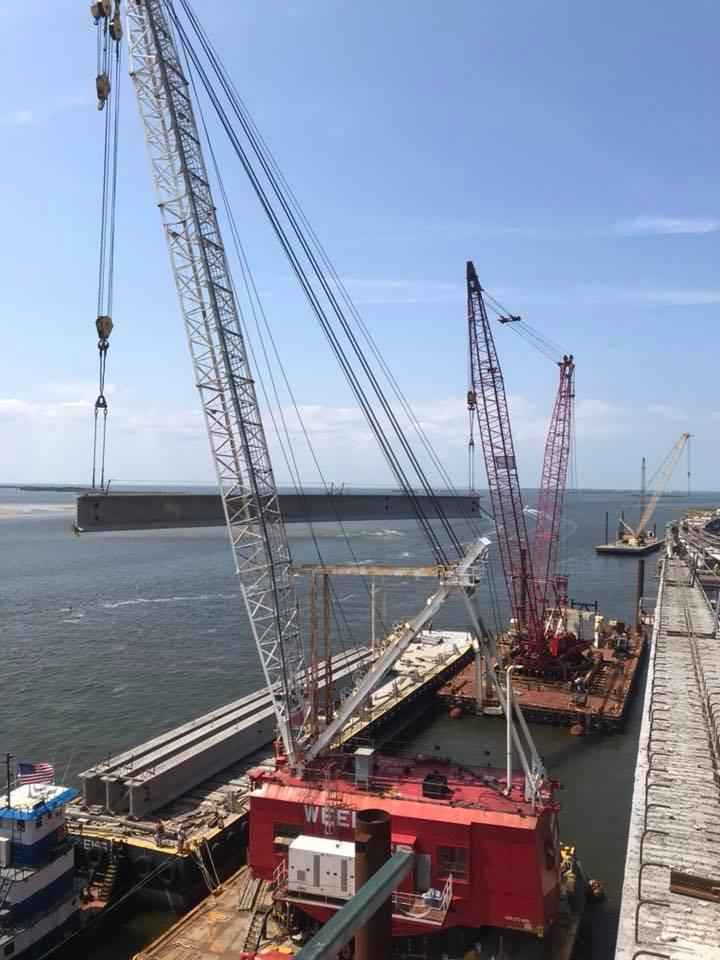 A crane lays the final girder on the Bonner Bridge replacement project.