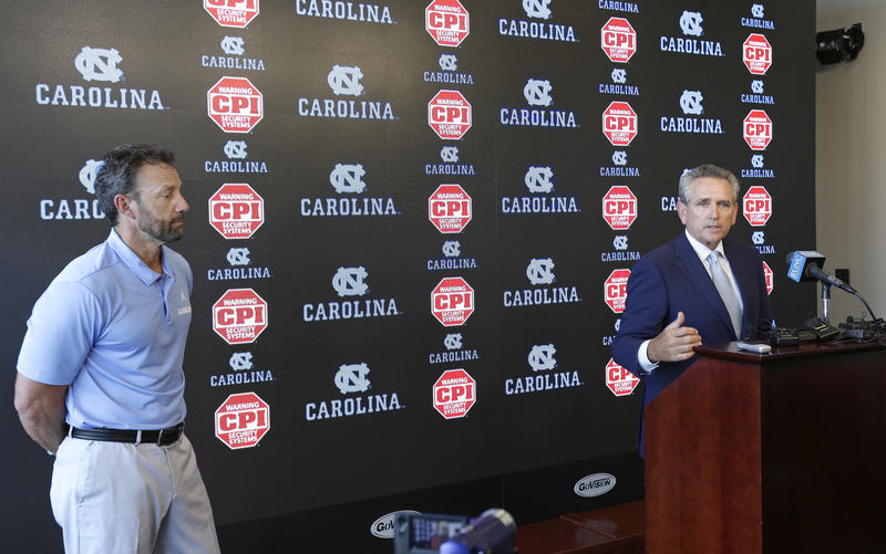 North Carolina coach Larry Fedora, left, listens as athletic director Bubba Cunningham makes comments during the NCAA college football team's media day in Chapel Hill, N.C., Monday, Aug. 6, 2018.
