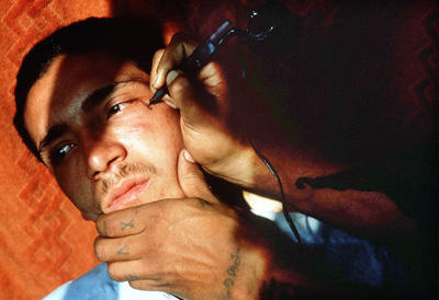 Los Angelos gang member being tattoed