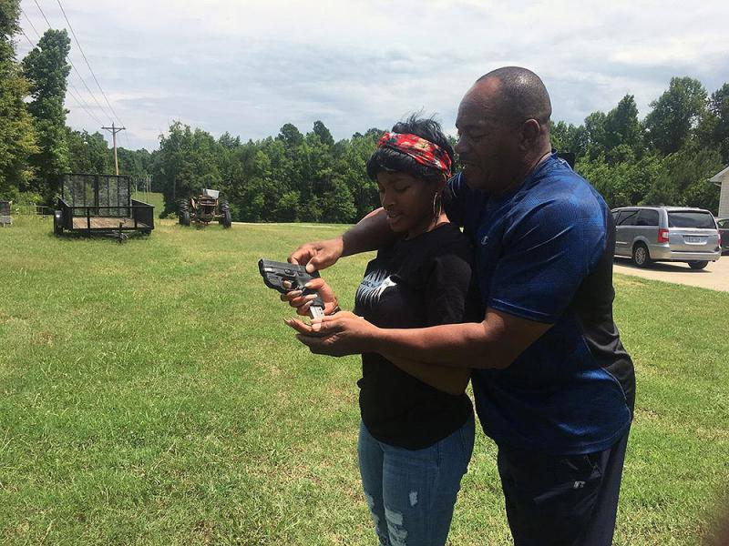 Kenzi Patrick with her grandfather James Patrick, who is teaching her how to safely reload a 9mm pistol on July 7, 2018.