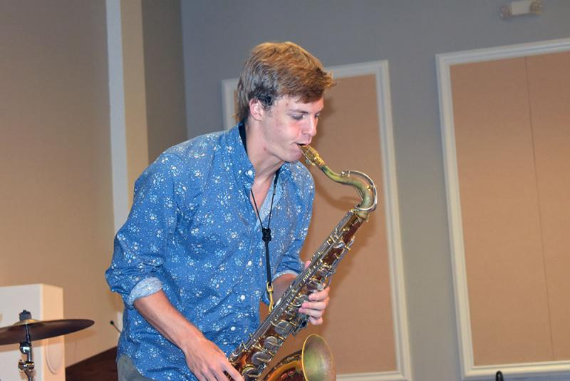 Hayden Davis plays the saxophone for residents