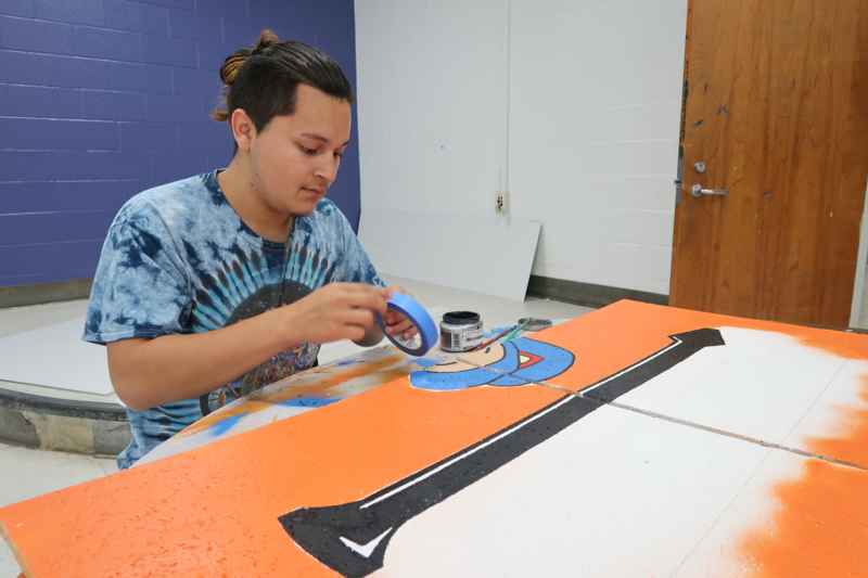 Alex Castorela paints a ceiling tile as part of his art internship at Vance County High. Castorela plans to attend community college and pursue his dream of becoming a tattoo artist.