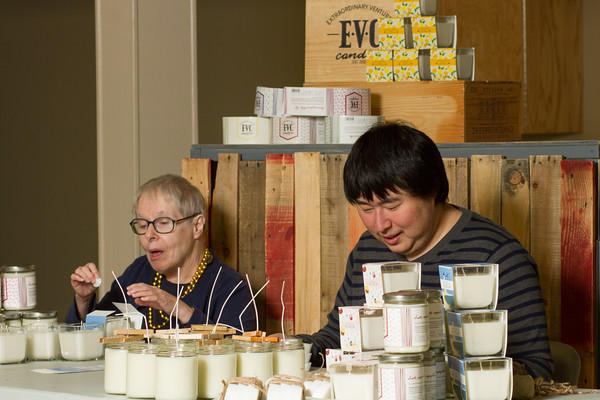 Two adults with developmental disabilities make candles.