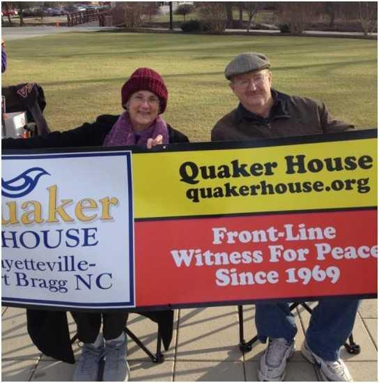 Lynn and Steve Newsom hold a banner for Quaker House