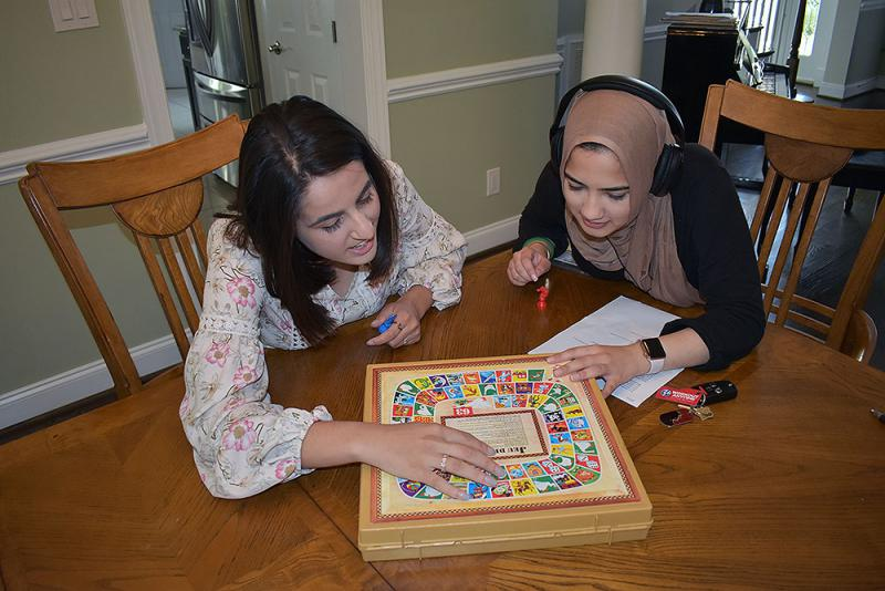 Safia Ghafoor, shows Zara Ameera Khan her childhood board game in Jeu de L'Oie, which helped her learn French when she was younger.