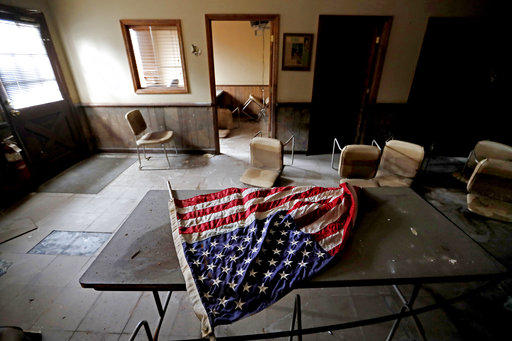 An American flag lays on a table in the old town hall which sits damaged from Hurricane Matthew's flooding two years ago in Nichols, S.C., Thursday, Sept. 13, 2018.