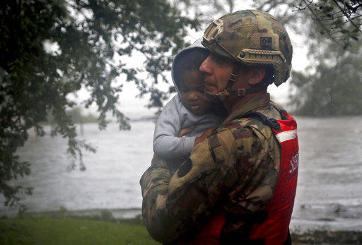 Rescue team member Sgt. Nick Muhar, from the North Carolina National Guard 1/120th battalion, evacuates a young child as the rising floodwaters from Hurricane Florence threatens his home in New Bern, N.C., on Friday, Sept. 14, 2018.