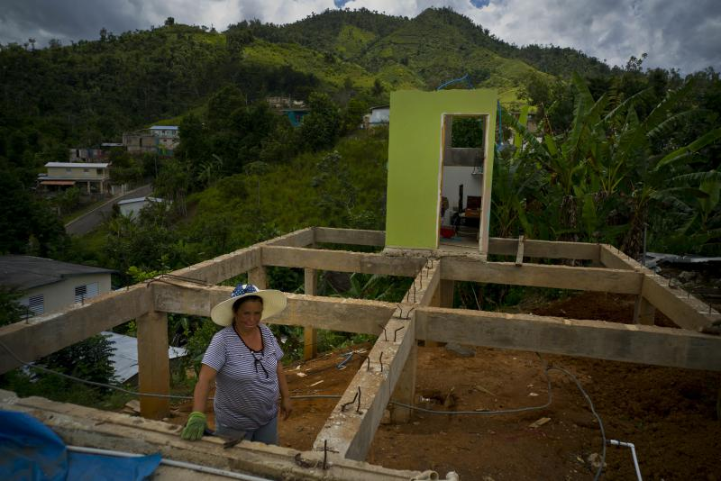 In this Sept. 8, 2018 photo, Alma Morales Rosario poses for a portrait between the beams of her home being rebuilt after it was destroyed by Hurricane Maria one year ago in the San Lorenzo neighborhood of Morovis, Puerto Rico.
