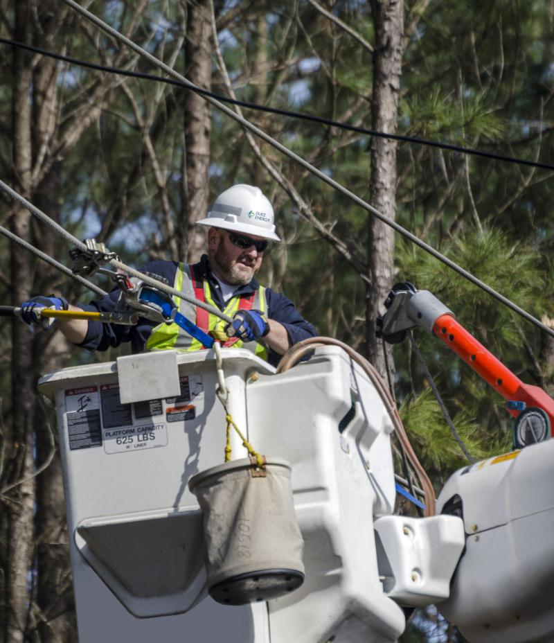A Duke Energy worker restores power after a storm.