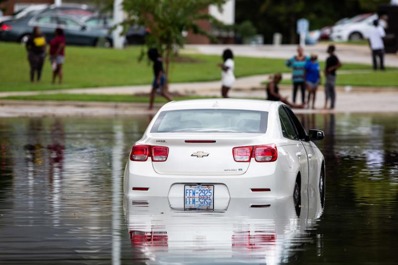 Residents of an apartment complex in Fayetteville, look at a flooded car in a parking lot on Tuesday, Sep. 18, 2018.