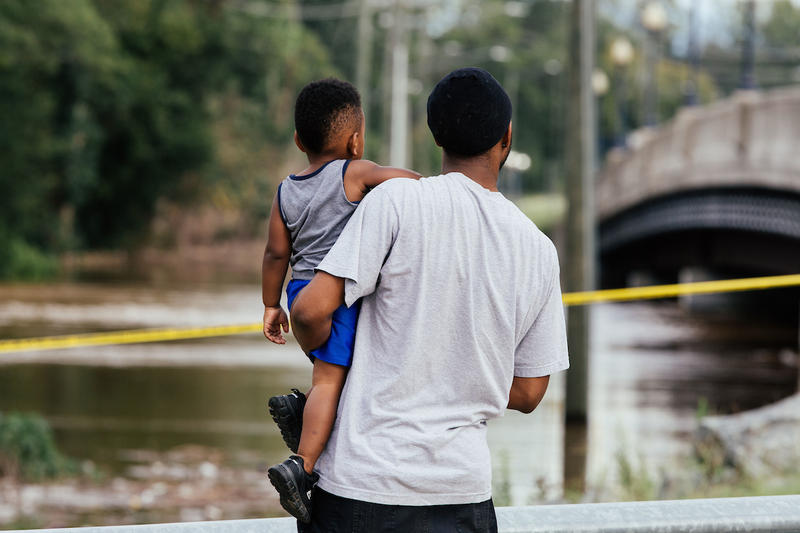 A man and boy stand and watch as the quickly rising Cape Fear River threatens the bottom of the Person Street bridge in Fayetteville, N.C., Tuesday, Sep. 18, 2018.