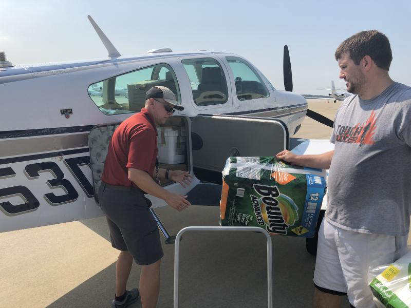 At RDU, Ben Akroyd helps pilot Martin Fessele pack his Beechcraft Bonanza aircraft with supplies for victims of Hurricane Florence.  Fessele came from New Jersey to help with 'Operation Airdrop.'