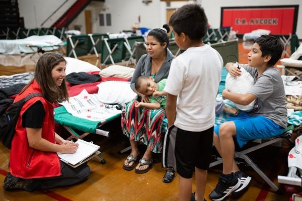 Beatriz Jerlen Covarrubias-Rivera relaxes on a Red Cross cot with her four sons, ages 2 to 10, while staying at a shelter operated by the Red Cross at E.B. Aycock Middle School on Saturday, Sept. 15, 2018.