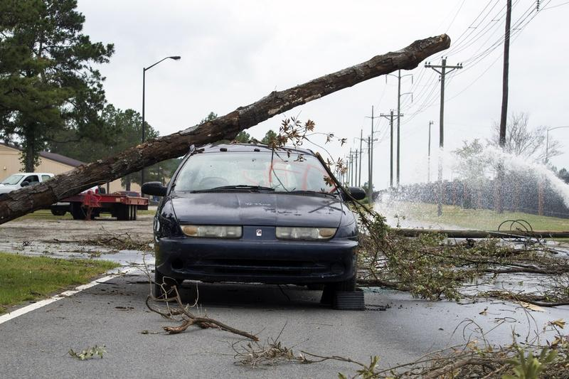 A light pole leans on a car as Hurricane Florence made it way across North Carolina on Friday, Sept. 14, 2018.