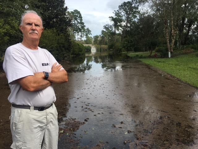 John Nemeth stands in front of a flooded road in the River Landing neighborhood of Wallace