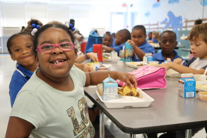 Students Kamora Foxworth, left, and Odyessi McDougald, center, smile while they eat lunch at Southside-Ashpole Elementary on the first week of school as the elementary becomes the first in the state's Innovative School District.