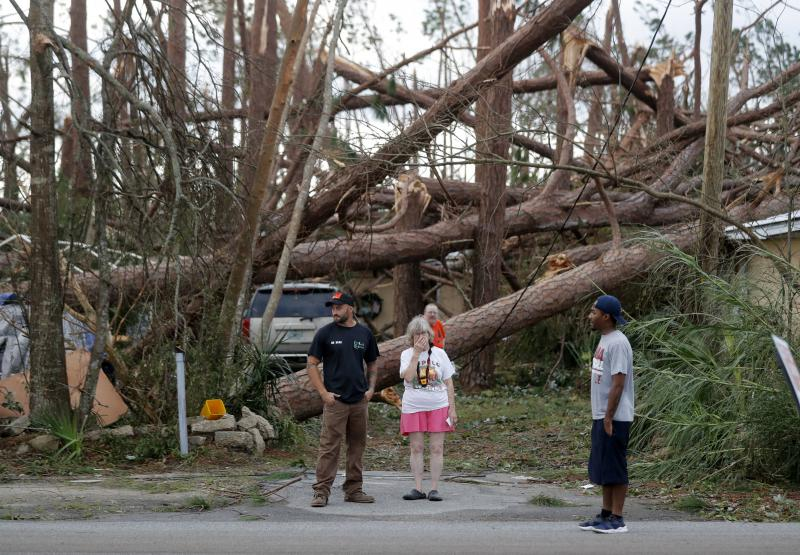 Joyce Fox, center stands in front of her heavily damaged home in the aftermath of Hurricane Michael in Panama City, Fla., Thursday, Oct. 11, 2018.
