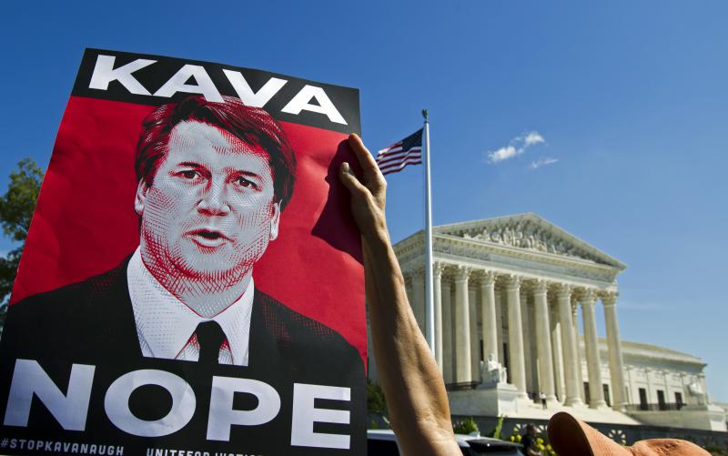 "a poster of Brett Kavanaugh that says ""Kava Nope"" in front of the Supreme Court Building in D.C."