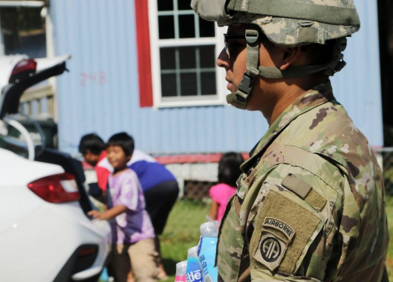 Spc. Alvarez carries a package of bottled water to a family in New Bern, North Carolina, Sept. 21, 2018.