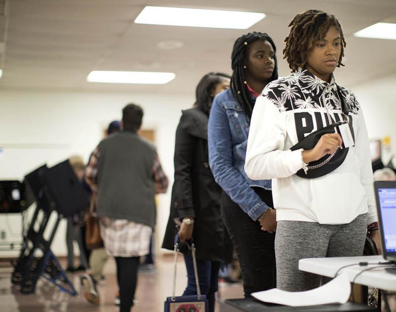 Bennett College students, Nia Watson, right, Ariel Tindle and Destiny Edward wait in line to vote early at Brown Recreation Center on Friday, Oct. 19, 2018, in Greensboro, N.C.