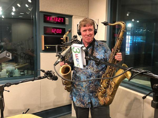 a photo of Jim Henderson holding two saxophones