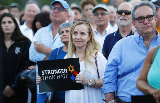 Iris Schaen, center, holds a sign as she listens to speakers during an interfaith vigil against anti-semitism and hate at the Holocaust Memorial, Tuesday, Oct. 30, 2018, in Miami Beach.