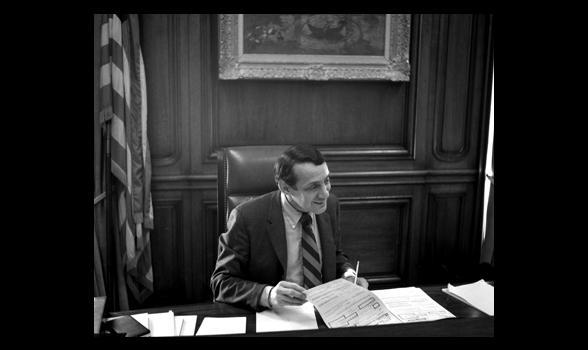 a photo of Harvey Milk at Mayor Moscone's desk