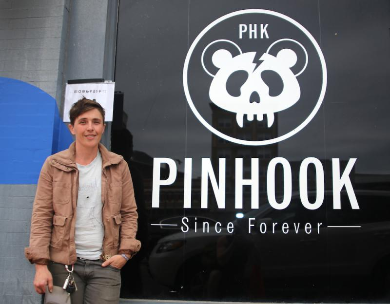 Kym Register standing in front of The Pinhook's logo