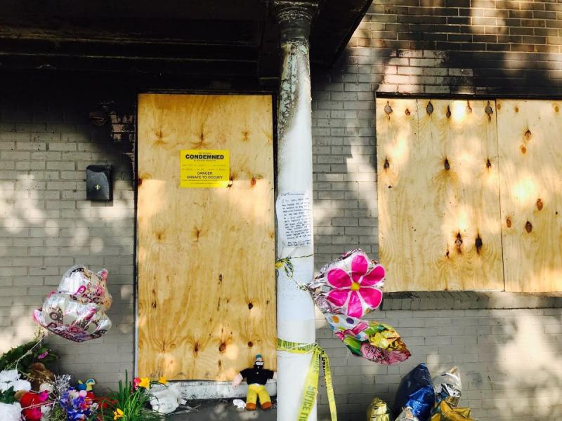 A boarded up apartment entrance as a makeshift memorial