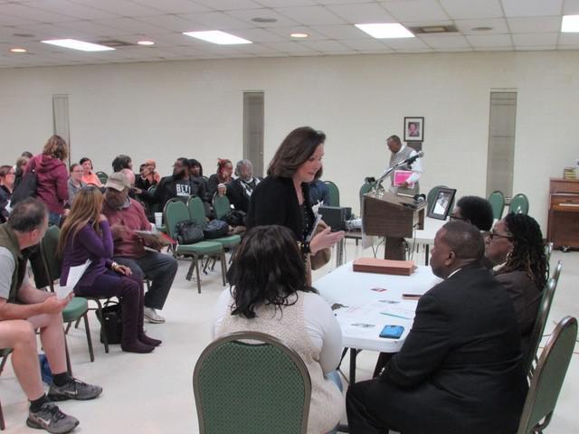 photo of Mayor Nancy Vaughn at table talking to people.