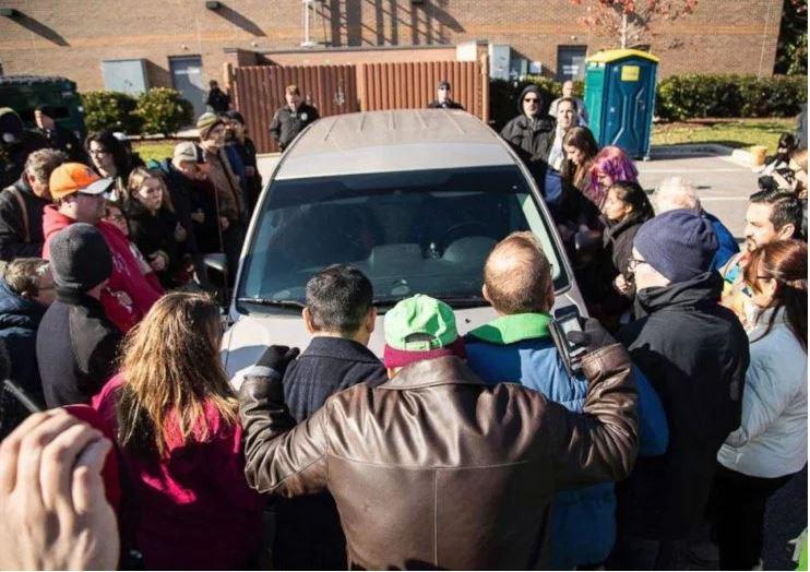 Protestors surround a car