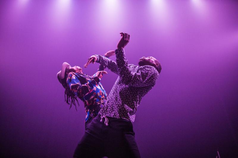 Jon Boogz and Lil Buck dance in purple light.