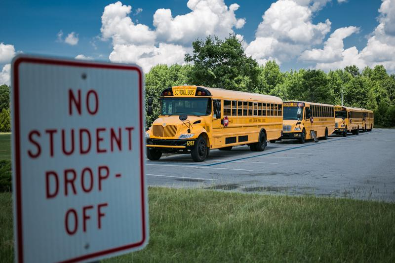 A sign indicates a no-student drop-off zone with Wake County public school buses in the background.